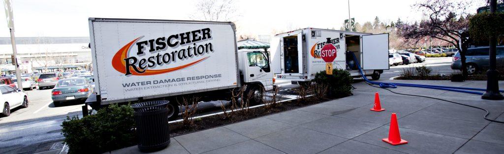 Fischer Restoration water damage trucks at worksite