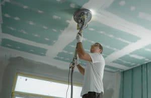 man finishing repair after ceiling leak