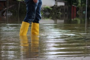 person wading through flood water in rubber boots