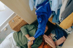 person lying on the floor of a crowded closet