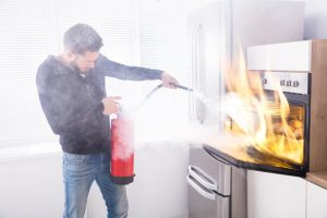 man attempting to extinguish a fire in the kitchen